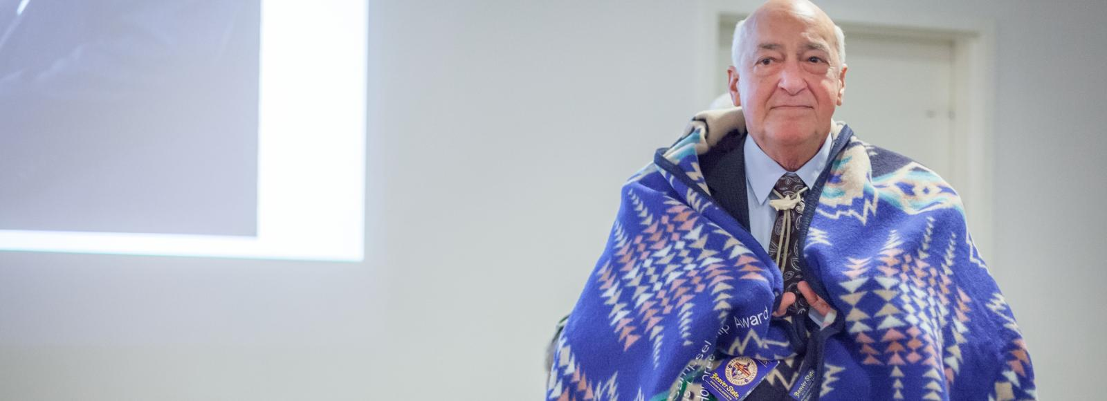 Blanketed in a Pendleton blanket, indigenous leader Roy Sampsel is honored at the ILA ceremony
