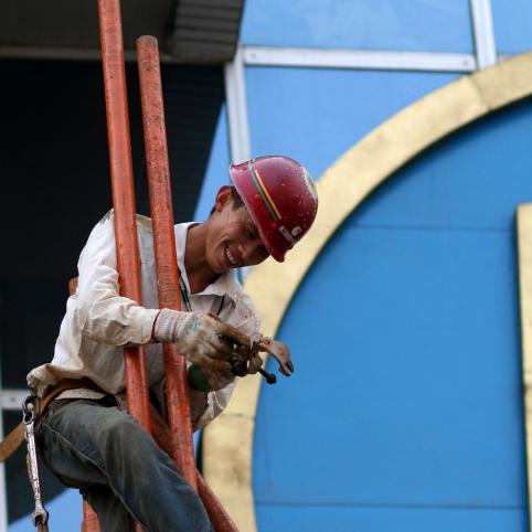 smiling worker in hardhat, blue building behind him, asian man