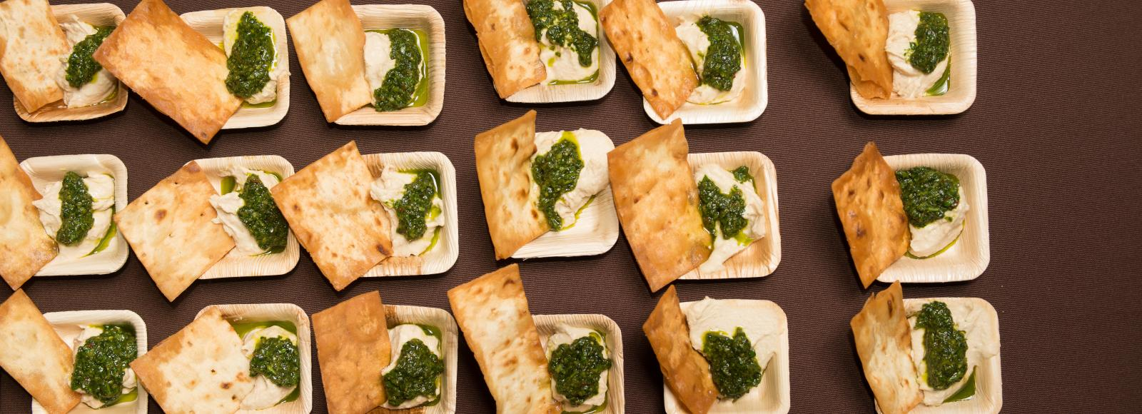 food samples in little trays with hummus, cilantro sauce and a cracker