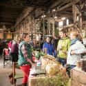 People gathering in old warehouse talking with farmers at a fair