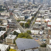 Aerial view of a building, the Bullitt Center, with solar panels on the roof. A city skyline, Seattle, is in the background.