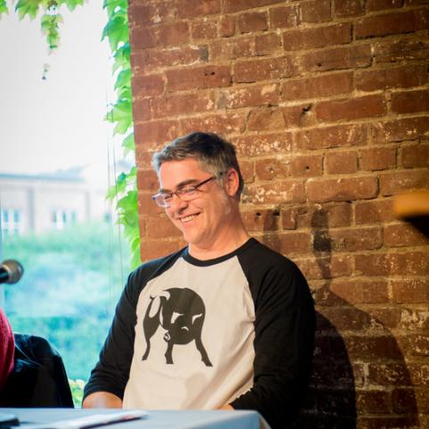 Aaron Silverman sits on a panel in a black and white long-sleeved t-shirt with a brick wall behind him