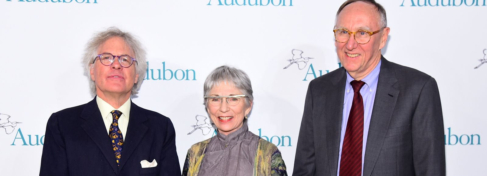 Two men and a woman stand in front of a white screen with the logo of Audubon