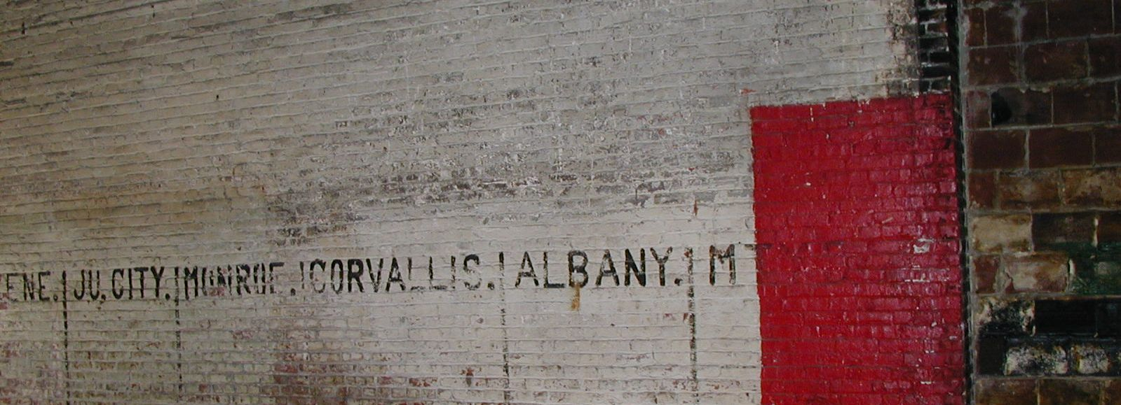 old brick warehouse wall, painted with the names of Oregon cities, Ecotrust