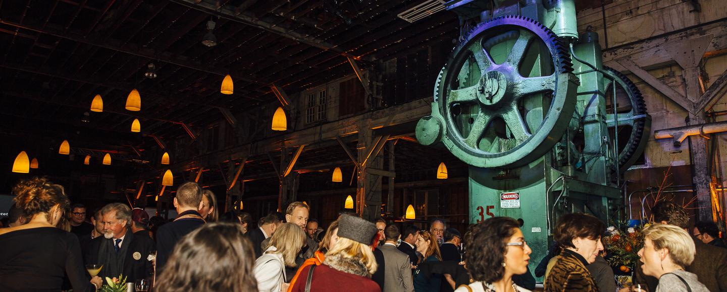 large green iron stamping press lit up with event goers mingling underneath