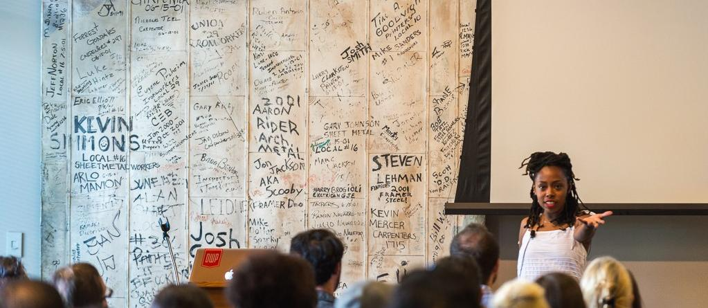 Woman standing in front of wall covered in signatures, speaking to seated crowd in conference room