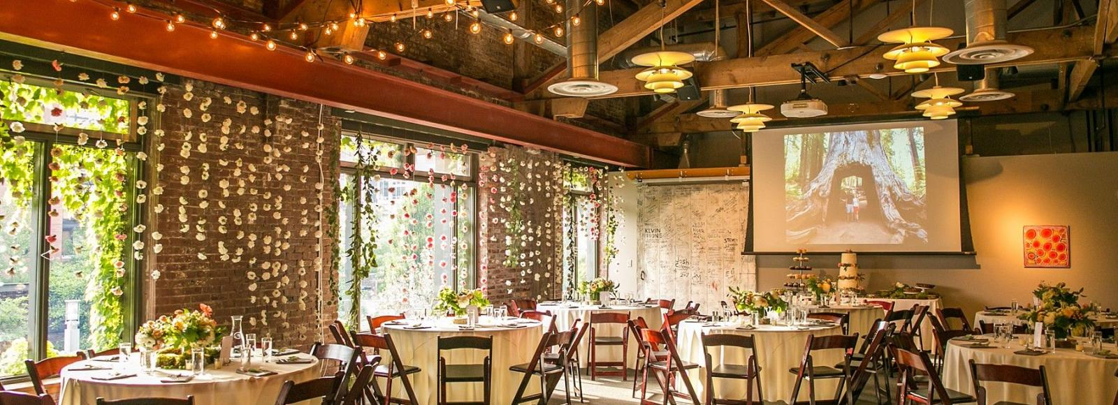 Dance floor surrounded by round table seating with hanging lights and high ceiling beams in the Ecotrust conference room
