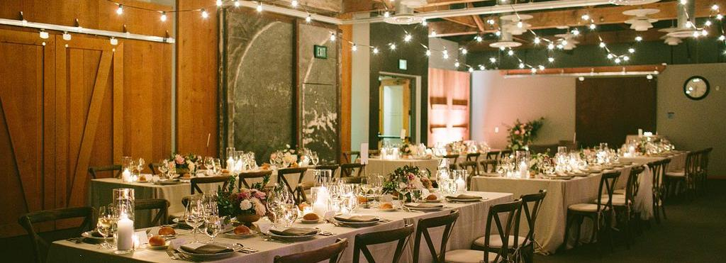 Banquet seating in conference room with flowers, tea lights, and cafe lights with cement wall at the Ecotrust building in downtown Portland