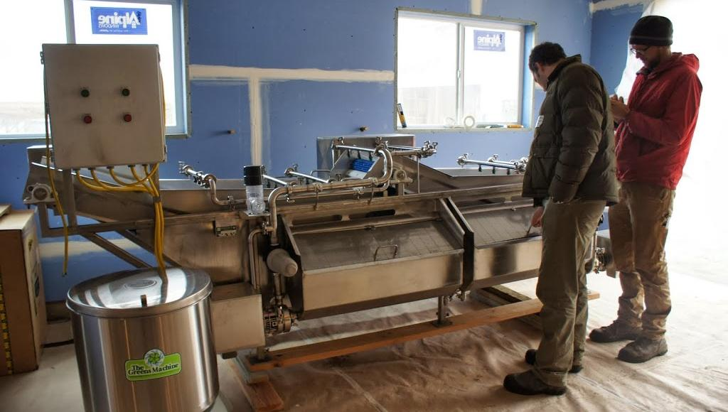 Two farmers look at a large piece of commercial processing equipment at Cloud Mountain Farm Center; they are in a blue, unfinished room.