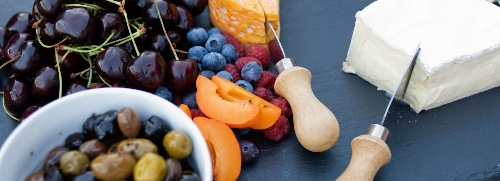 A cheese plate with fruit and olives is displayed on a stone platter