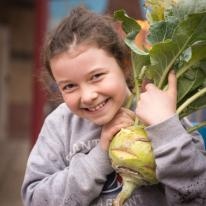 Middle school age girl hugs freshly harvested kohlrabi