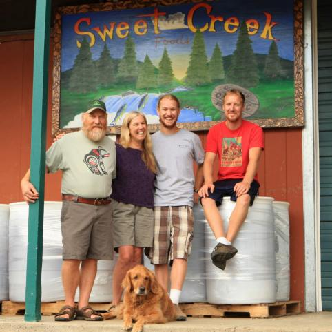 The Fuller family, standing with their dog in a portrait in front of a sign painted with the name of the company they run, Sweet Creek Foods.