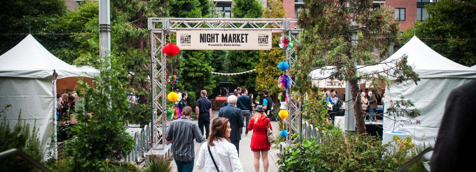 people walking into an outdoor party, tents, brick warehouse, greenery, Feast, Portland Ecotrust