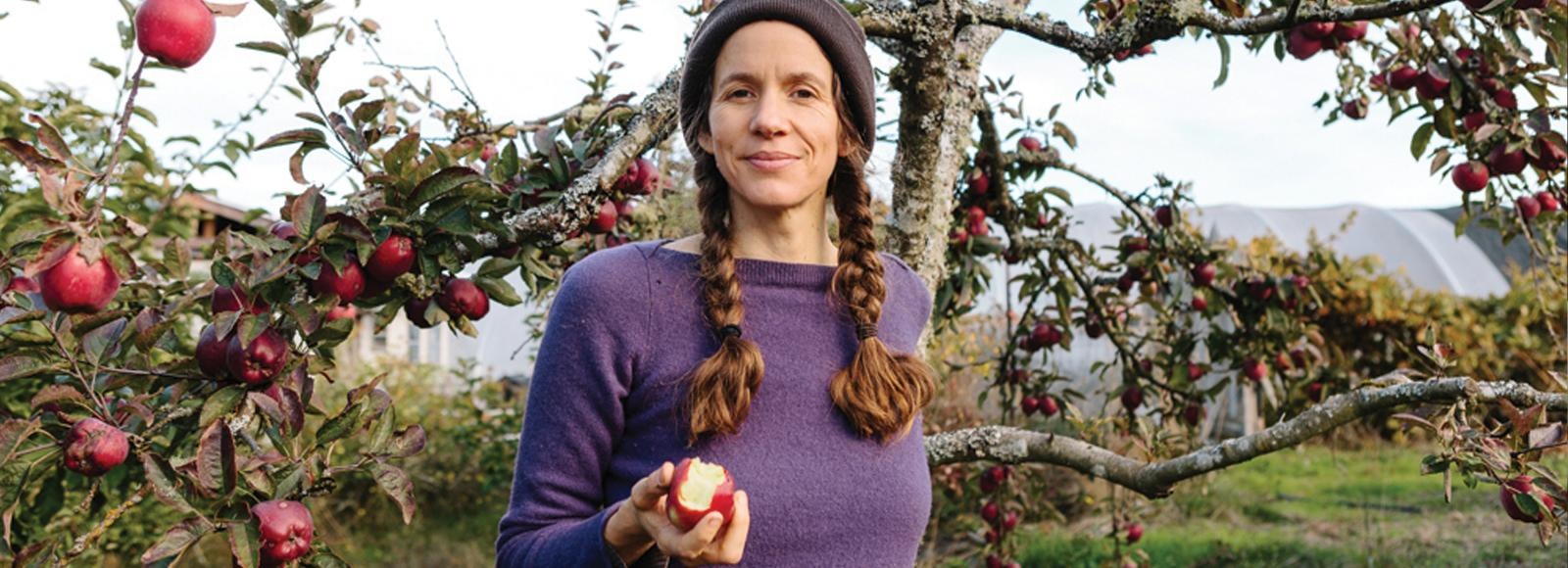 Woman in stocking cap and purple sweater with long pig tails holds an apple standing in front of a tree.