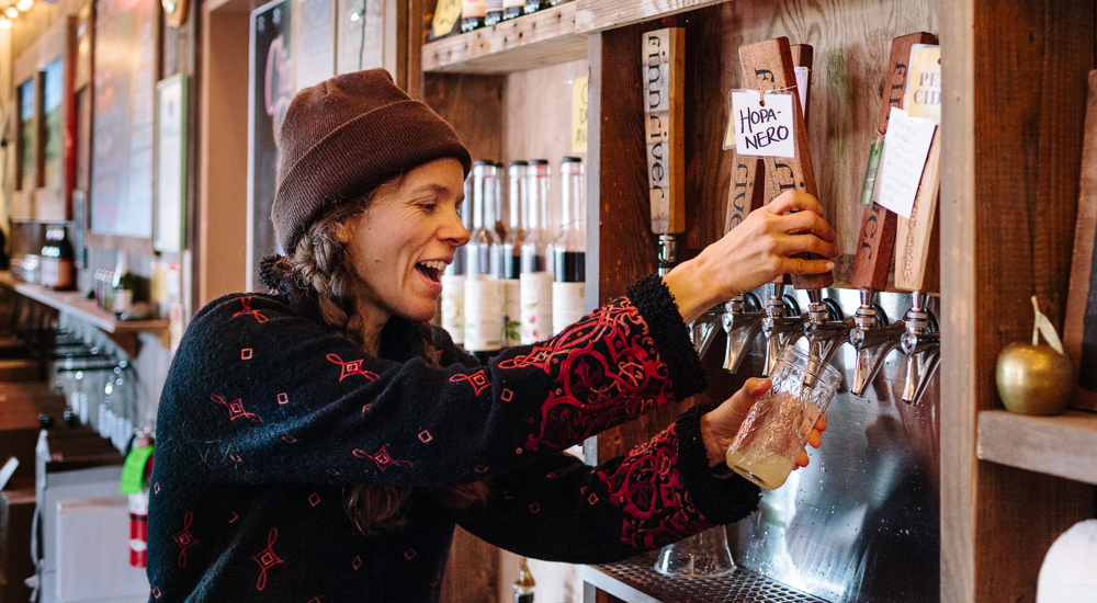 smiling woman in brown stocking cap and black and red sweater pulls wood handle to pour cider