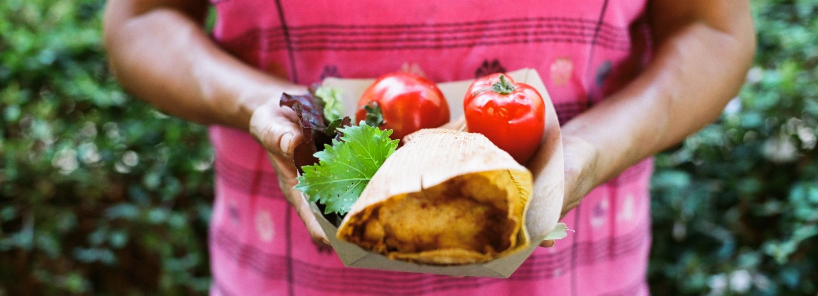 Women holds a tamale with two red peppers and greens
