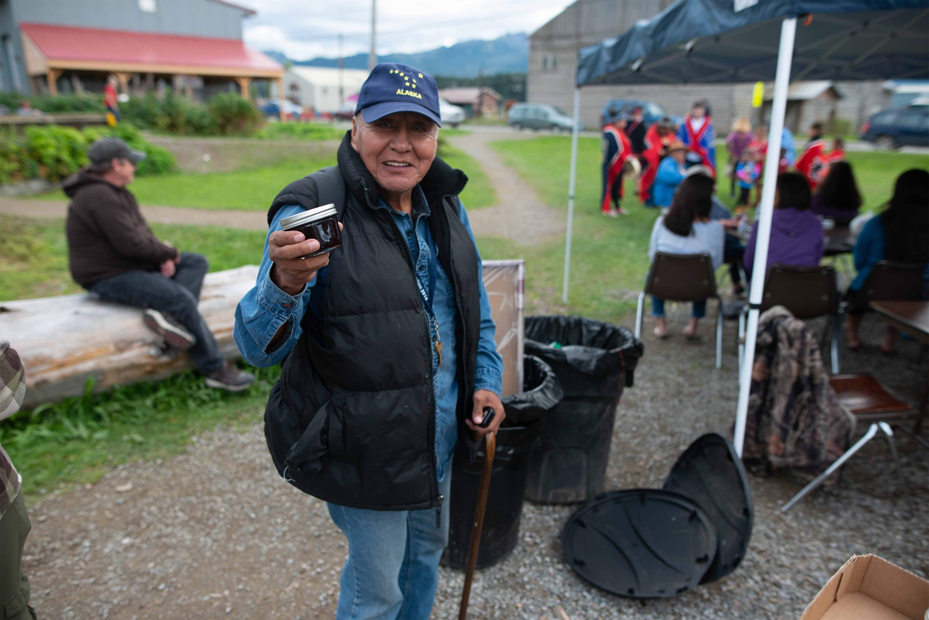 An eldery Tlingit man wearing a blue Alaska hat and a puffy black vest smiles while holding a small jar of blueberry jam.
