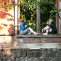 Two women facing away from the camera, perched on a brick wall, dappled sunlight, trees