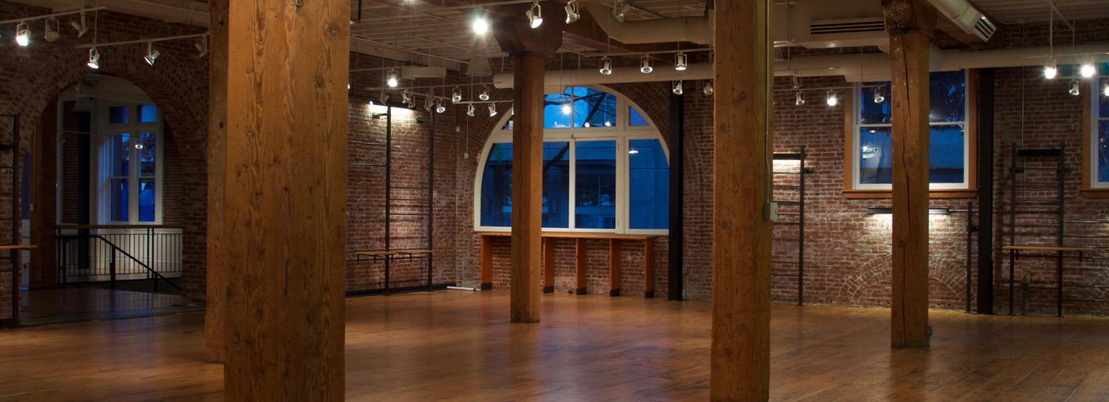 Empty event venue with wood beams and floors and brick walls