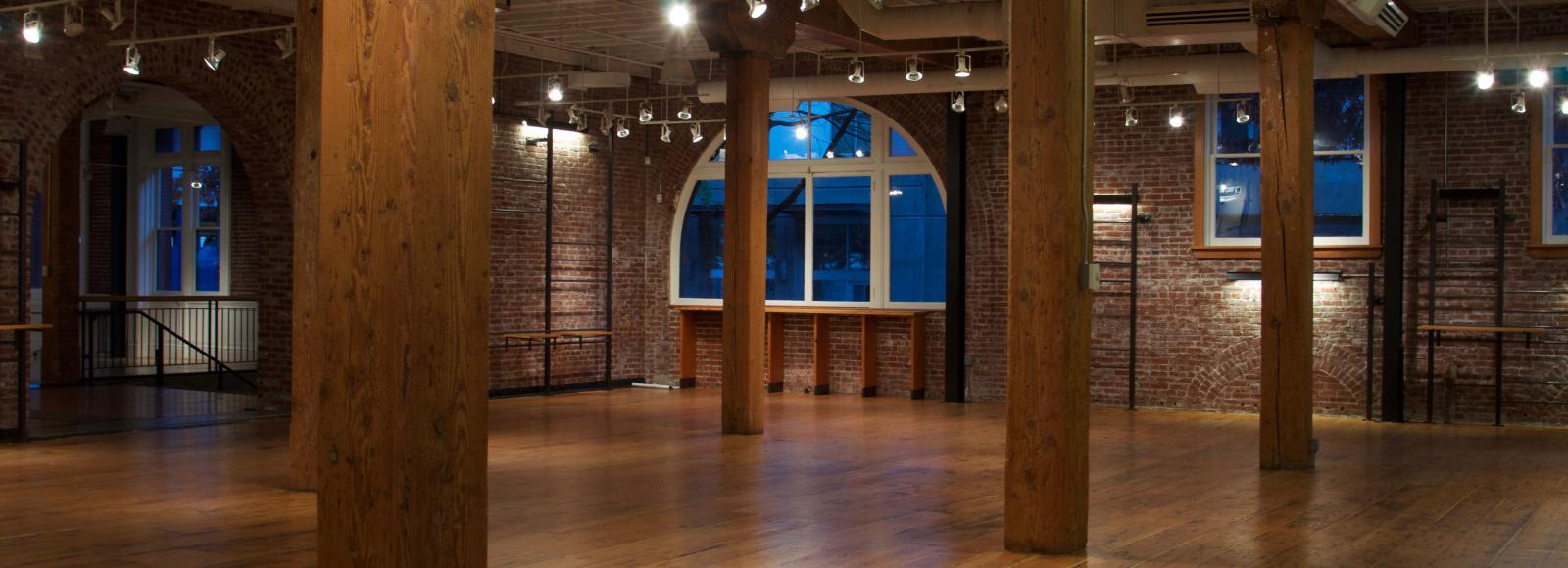 empty Irving Street Studio event space with brick walls, arched windows, and doug-fir columns