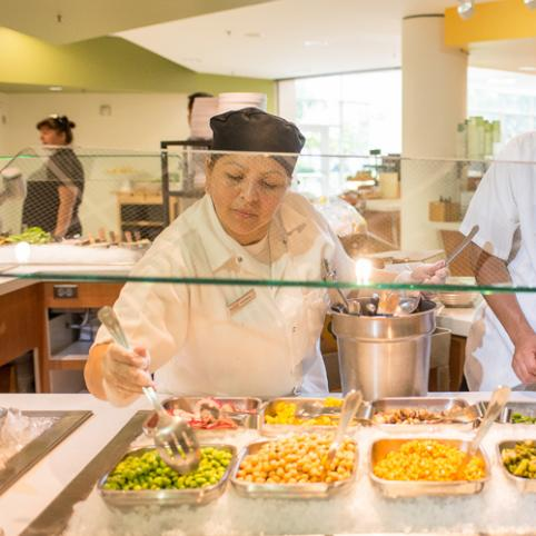 A woman in white jacket and black chefs hat prepares vegetables at a salad bar