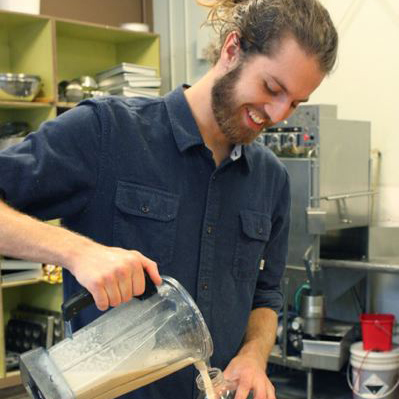 Smiling, bearded man in blue shirt pouring white liquid into clear glass jar.