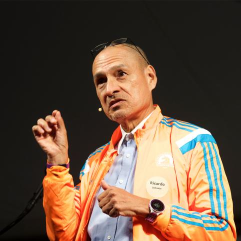 Man in orange jacket speaks from a stage