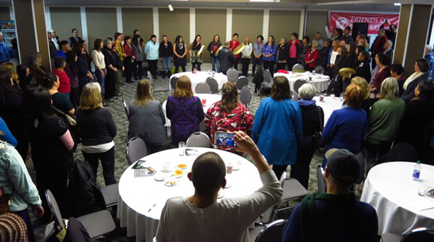 many people stand in a circle in a conference room at a Salmon Nation summit