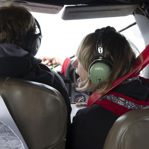 woman with headphones on in the cockpit of a plane talks to the pilot