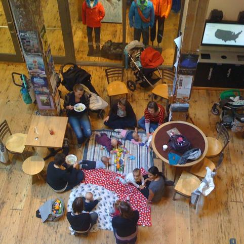 babies and moms hanging out in a wood-floored building, shot from above, looking down, Ecotrust
