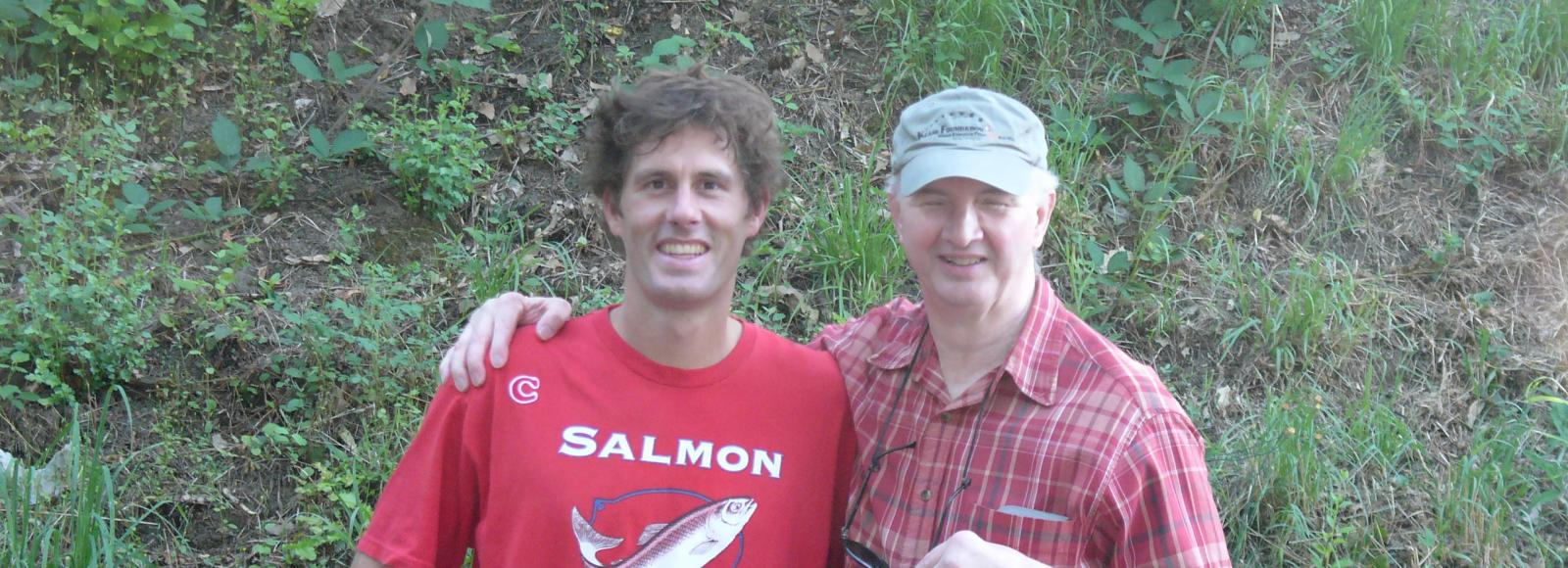 two men stand outside, one wearing a salmon nation bright red T-shirt