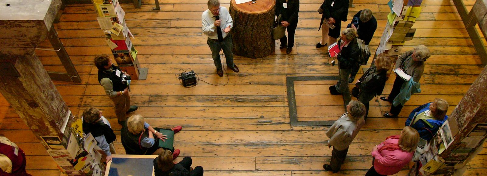 A view looking down into the atrium of the Natural Capital Center, which is full of light. A group surrounds Spencer Beebe, Ecotrust founder, who is standing next to a tall stump talking into a microphone.