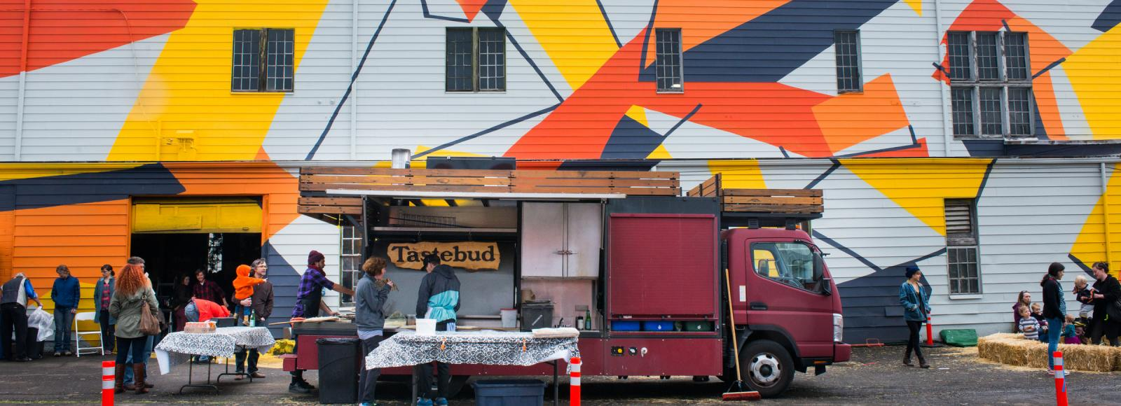 The Tastebud pizza mobile parked outside the Redd. The bright mural on the side of the Redd in full view.