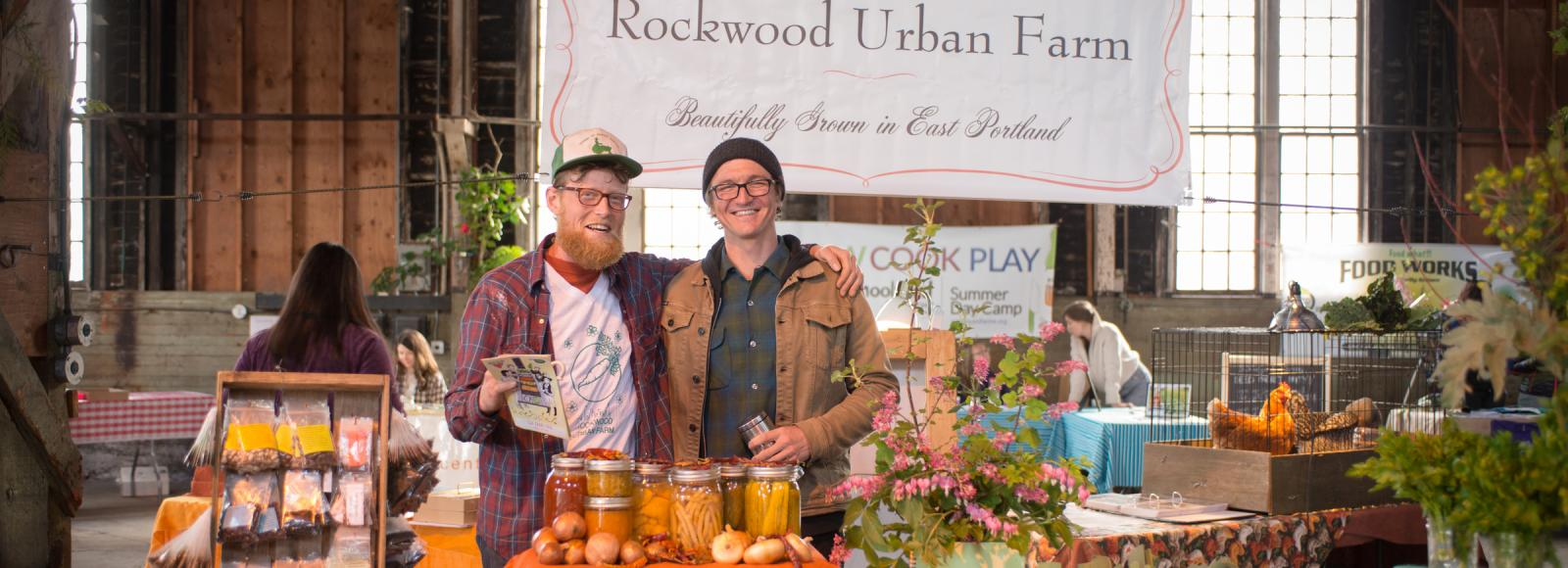 Two farmers from Rockwood Urban Farm stand at their booth, behind a pile of beans