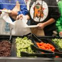 Kids line up in front of a salad bar cart including black beans, carrots, and snow peas at Parrish Middle School in Salem, Oregon.