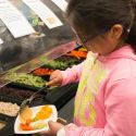 Middle school student dishes up fresh fruits and veggies from a cafeteria salad bar