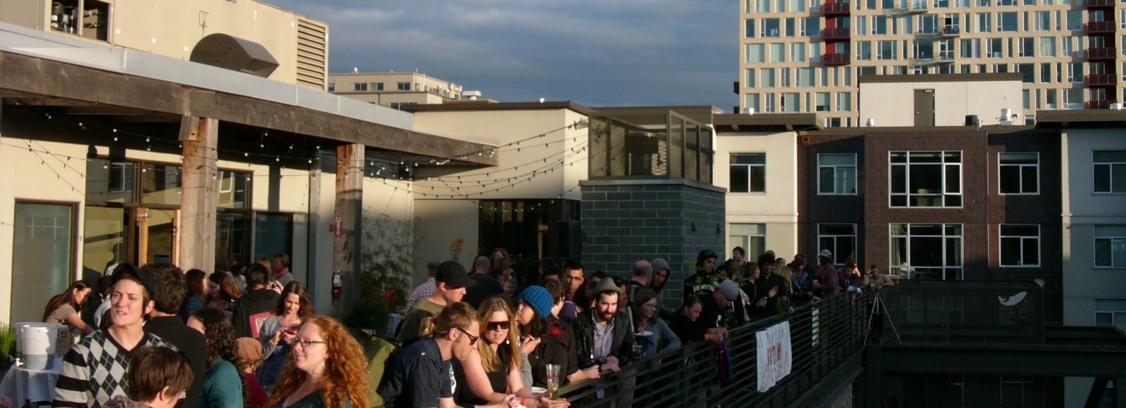 Smiling young people drinking and talking on the roof of a building in the city, sunny, portland, Ecotrust