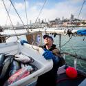 commercial fisherman helps move crate of fish
