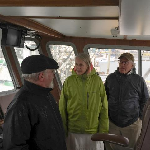 three people stand inside a boat