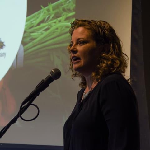 woman stands and speaks into a microphone with a slide deck showing a photo of veggies in the background