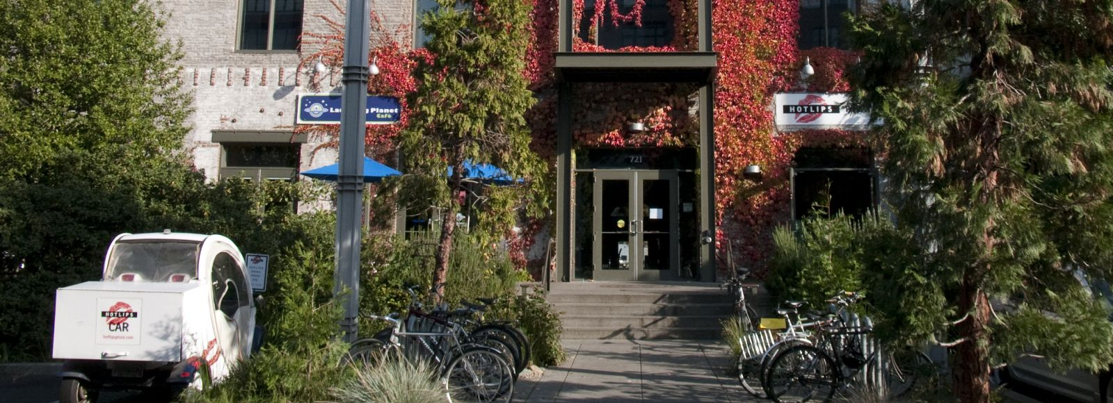 front of a brick building, ecotrust, portland, huge red vine growing up the front, fall sunshine