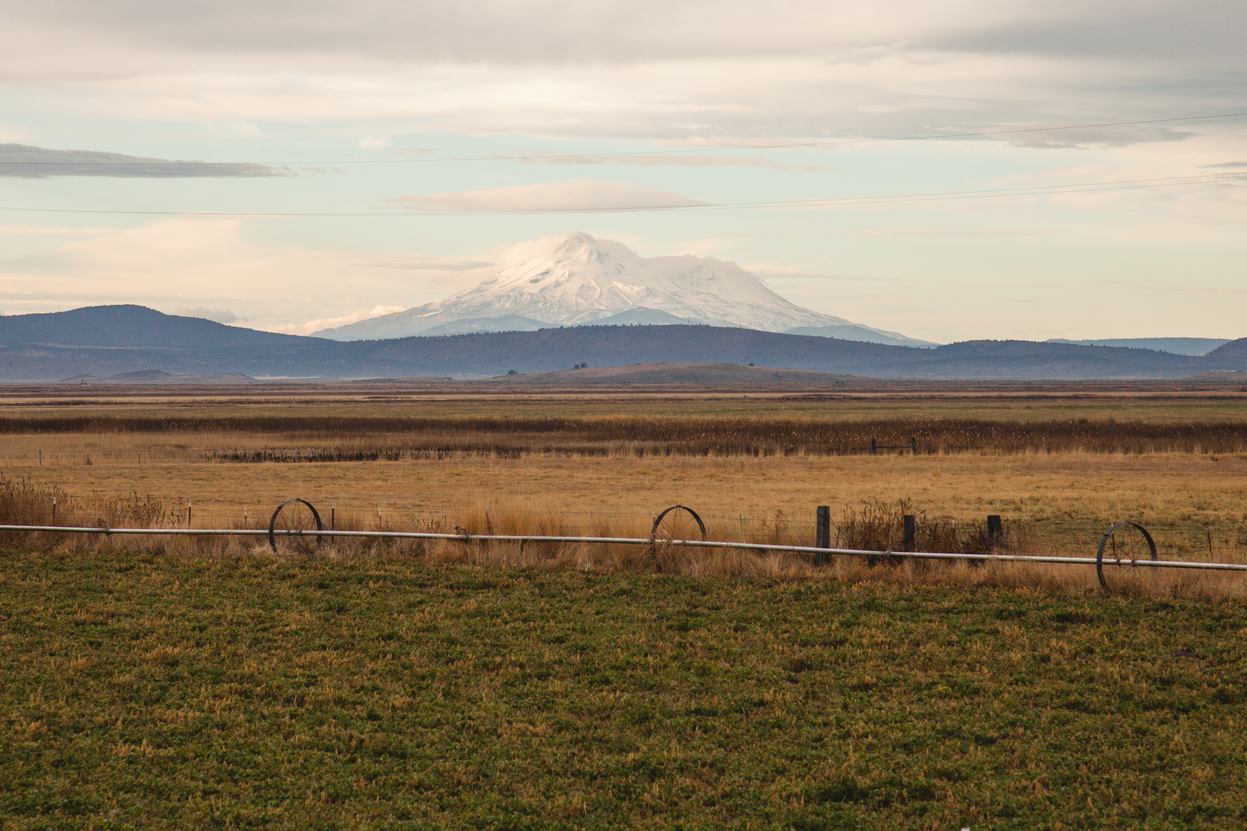 View of farmland with a snow-capped mountain in the distance