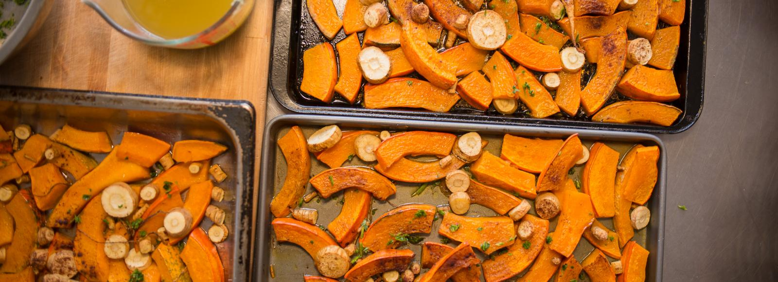 Trays of roasted squash and parnsnips rest on a butcher block table next to a pitcher of yellow oil or butter.