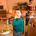 Child waiting for lunch in school with a hand over his mouth.