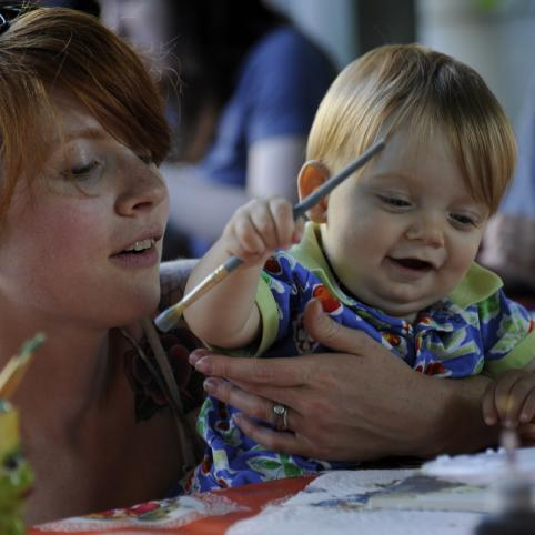 young mother and toddler - close up, smiling, child is painting with mom's help