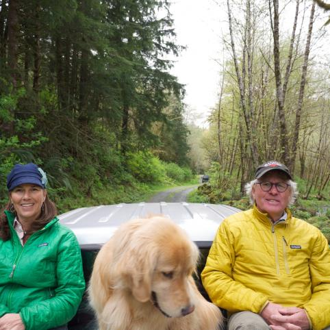In the middle of a forest, a large golden retriever sits between Bettina and Spencer in baseball caps