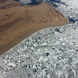 aerial shot of ice meeting land in the arctic, a beautiful pattern is created, brown land, white and dark blue ice