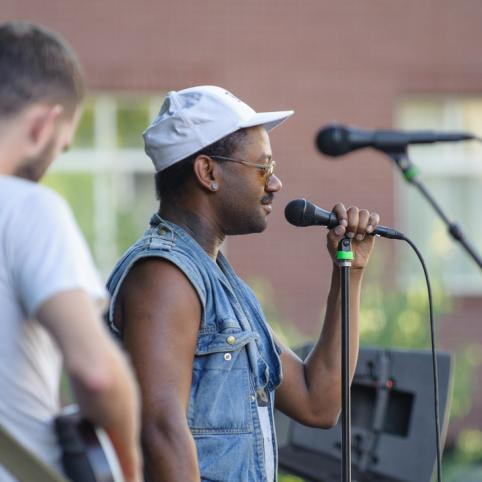 man in baseball cap sings into a microphone on an outdoor stage
