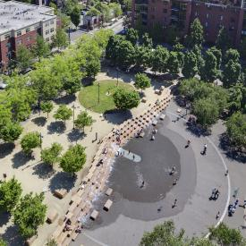 aerial photograph of a green, attractive city wit brick buildings, a park with a fountain, and people out enjoying themselves. Portland, OR - Pearl District, Jamison Square, Natural Capital Center