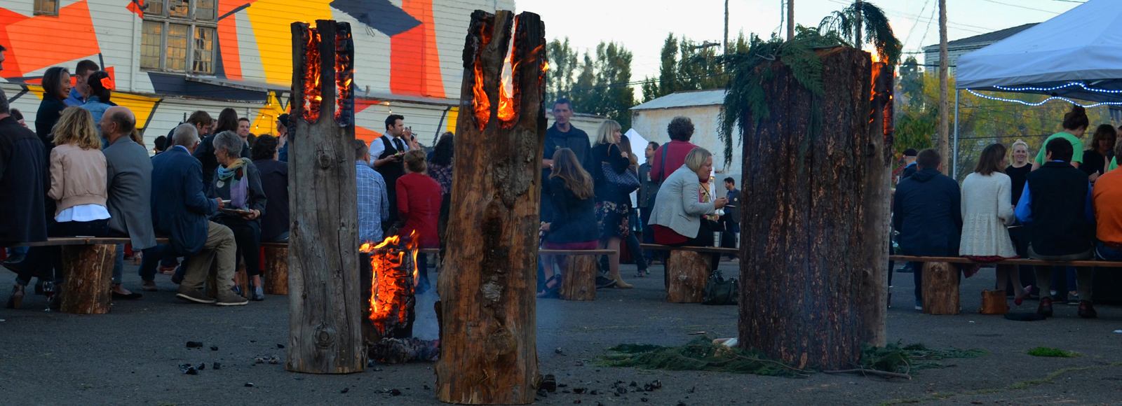 Three large logs, standing vertically, on fire in front of a cheerful crowd of people, some sitting.